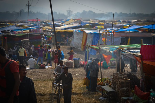 Buying and selling. I progressed to find a huge sprawl of colourful commercial stalls in the field near the wetland, lined with everything from clothes to food, toys to knives. People plunged in, some alone, some in groups, bargaining for a rupee or two to get the best deal. The deal I was hungry to see was being set up on the other side.