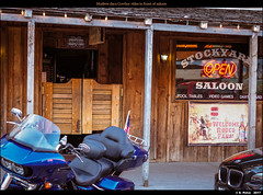 Modern days Cowboy rides in front of saloon