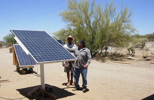 Community Coordinator Samuel Fayuant, right, explains the workings of solar panels to an engineering student from University of Massachusetts-Lowell.  The panels at Squash Burn Well in the Pisinemo District of Tohono O'odham Nation, Ariz., power the well's submersible pump.  Photo by Teresa Newberry