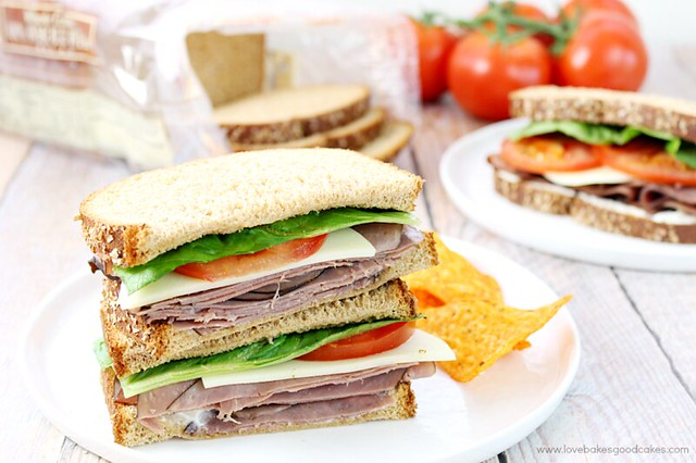 Roast Beef Sandwiches with Horseradish Mayonnaise stacked on a plate with red tomatoes and chips.