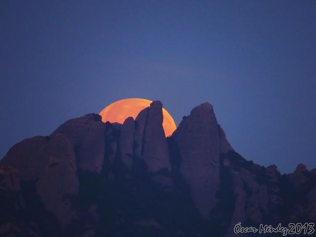 Luna llena anaranjada escondiéndose detrás de la montaña de Montserrat