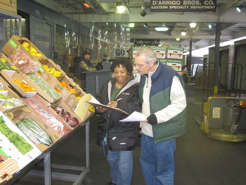 USDA Market News reporter Lynn Collins (left) from the Bronx, NY office gets prices from a sales rep at the fruit and vegetable terminal market.   For a few weeks in October when Market News reports weren't available, there was a higher risk that producers – especially small farmers and ranchers – would over-pay or under-price their goods.