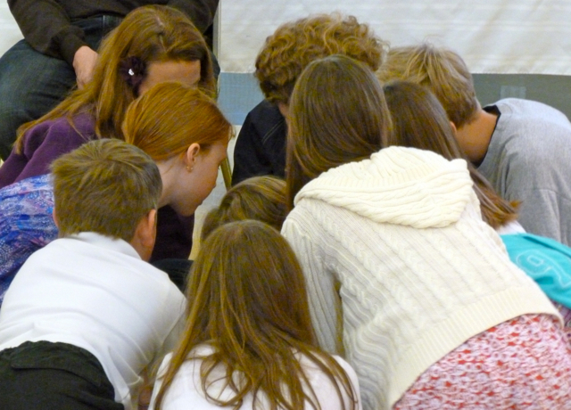 A group gathers huddles together to work on an answer at the Big Game