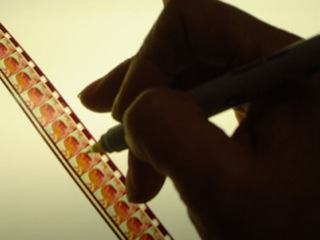 a hand painting a film strip frame by frame