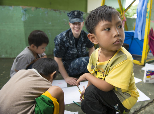 A boy looks away while drawing with Operations Specialist 2nd Class Heather Piersing