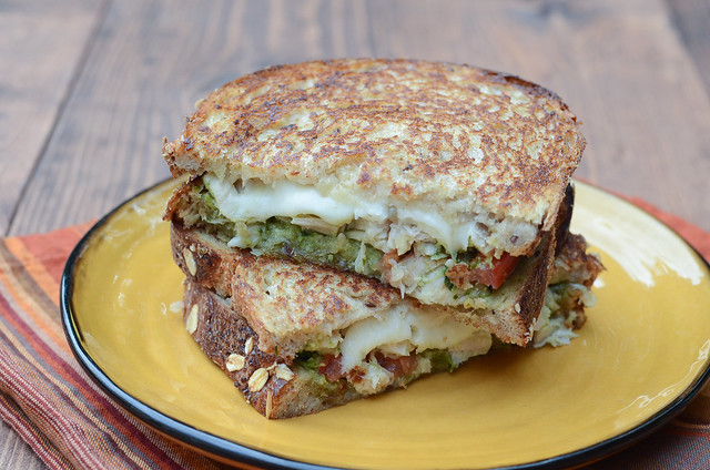 A Turkey Pesto Grilled Cheese Sandwich cut in half and stacked on a yellow plate.