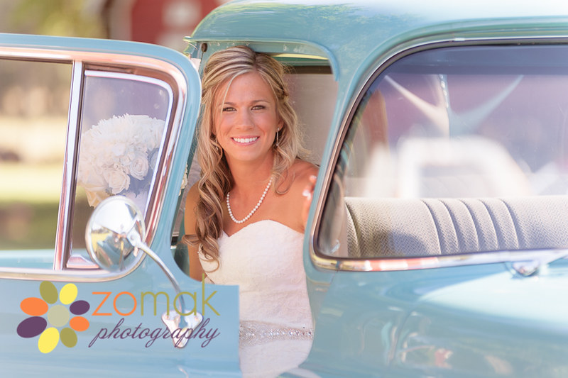 Beautiful bride poses in an aqua antique truck in rural Washington State