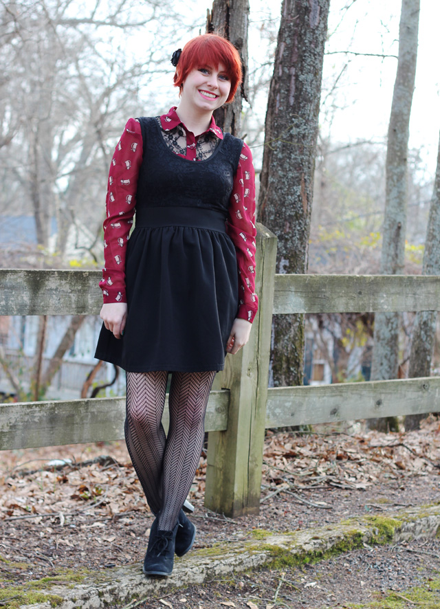 Sleeveless Black Dress over a Maroon Cat Print Shirt, Herringbone Patterned Tights, & Ankle Boots