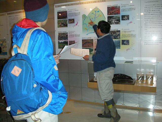 高原の自然館内のパネルでサンショウウオの分布を説明する内藤先生.