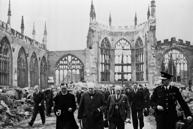 Prime Minister Winston Churchill walks with a guard and members of the Anglican clergy through the ruins of Coventry Cathedral. Official war photograph for the British government, 28 September 1941 by War Office official photographer Captain Horton