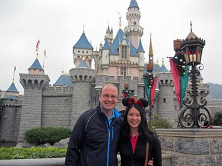 Mei and Dan outside Sleeping Beauty's castle in Hong Kong Disneyland.
