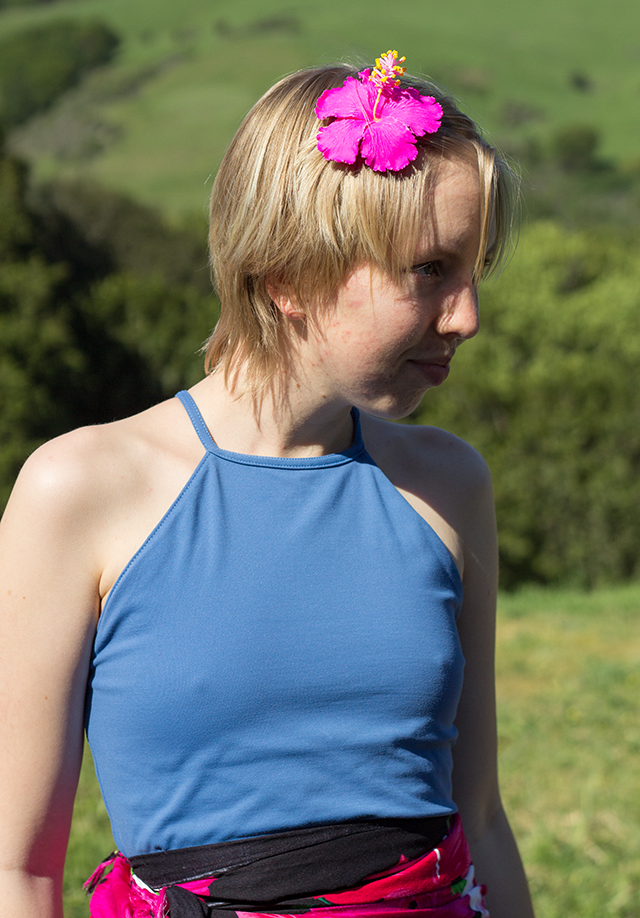 pink flower hair decoration, blue tank top