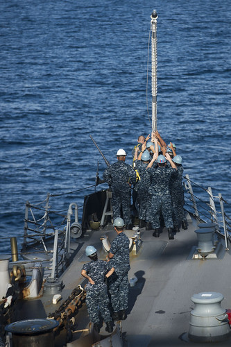 Sailors aboard the USS McCampbell (DDG 85) work together to raise the jack-staff
