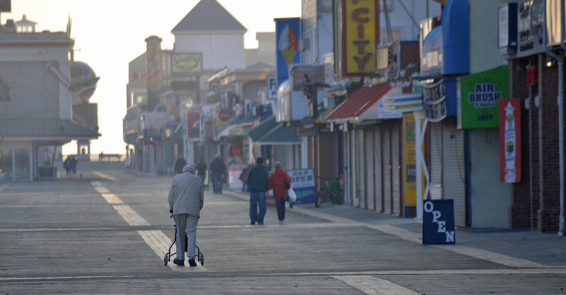 Elderly man walks with aid down boardwalk