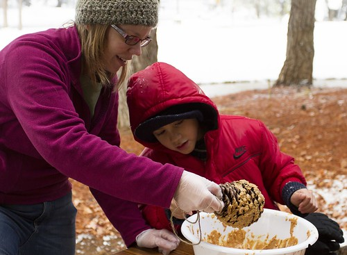 Ally Buccanero, Shasta College student and volunteer, demonstrates how to make a bird feeder using a large pine cone and peanut butter during Shasta-Trinity National Forest's annual Operation Christmas Tree event on Dec. 7. (U.S. Forest Service)