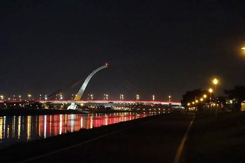 從河濱公園單車道望向夜間的大直橋,沿路照明足夠,往來運動的民眾頗多,十分安全。
