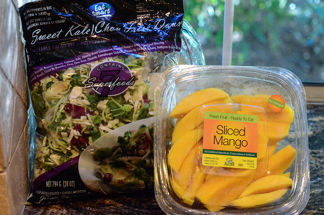 A bag of salad mix and container with sliced mangos.