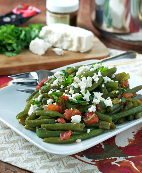 Spicy Braised Green Beans with Feta. A vegetable side dish with tomatoes, harissa, and feta cheese.