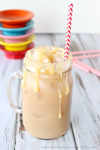 Iced Salted Caramel Latte in a glass jar with a straw and caramel dripping over the glass.