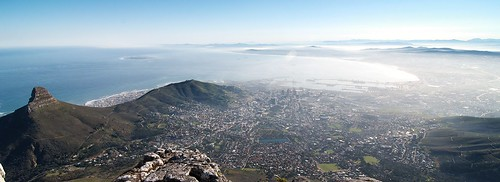rogersmj posted a photo:	An early morning view of a misty Cape Town from the top of Table Mountain. Lion's Head is at the extreme left, while Signal Hill juts toward Table Bay and the city center. Robben Island, where Nelson Mandela was incarcerated for 27 years, is visbile in the bay. The famous 2010 bird's-nest-style World Cup soccer stadium is visible just over the lower ridges of Signal Hill, left of center.