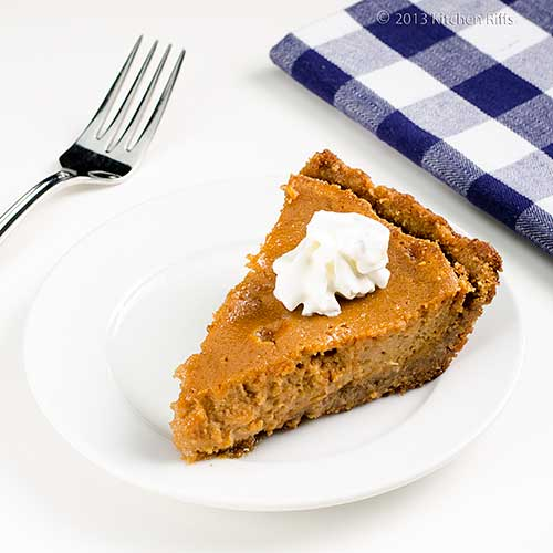 Sweet Potato Pie with whipped cream garnish, on plate with fork and napkin in background