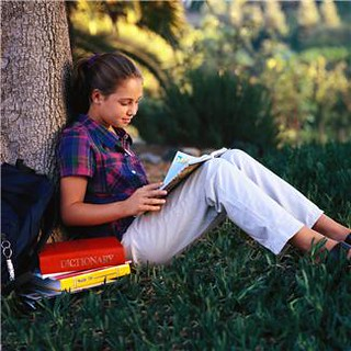 Girl reading magazine under a tree