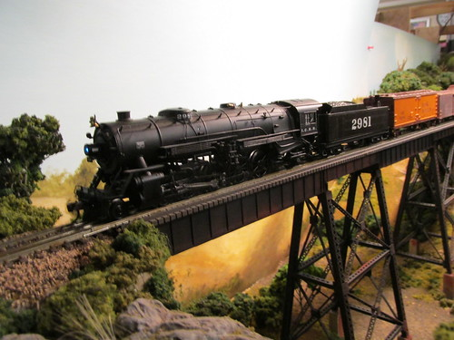 A steam powered Illinois Central Railroad freight train crossing the tall steel trestle.  The Oak Park Society of Model Engineers,H.O Scale Model Railroad Club.  Oak Park Illinois.  July 2013. by Eddie from Chicago
