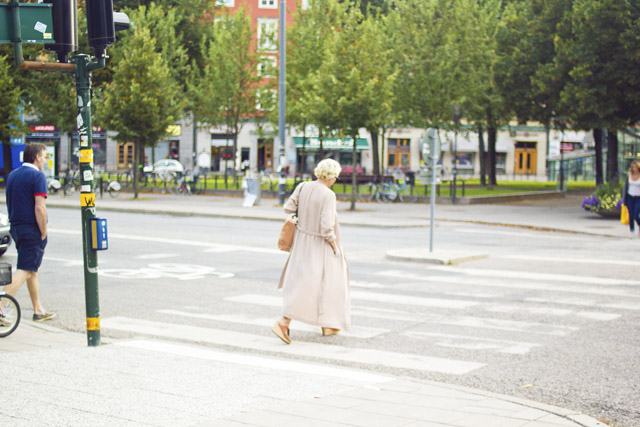 stylish woman crossing the road in Stockholm