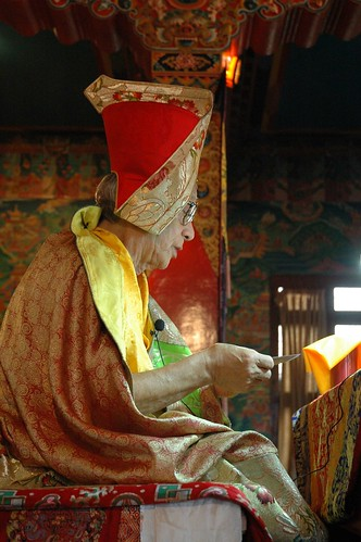 Guru Dagchen Rinpoche on his throne teaching at Sakya Lamdre, traditional silk robes, pecha, Sashu Hat (of the Sakya tradition), murals of the Buddha's life, Tharlam Monastery of Tibetan Buddhism, Boudha, Kathmandu, Nepal by Wonderlane