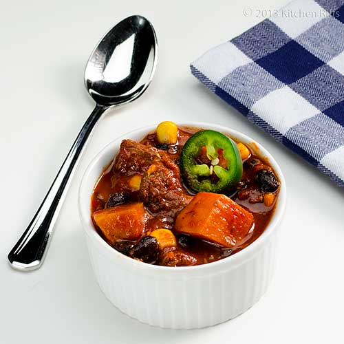 Chunky Pork and Sweet Potato Chili in ramekin with spoon and napkin in background