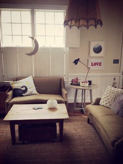 little living room, with vintage sofas in tweed and a sugarboo pillow