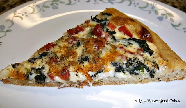 Tomato Spinach Alfredo Pizza slice on a white plate.