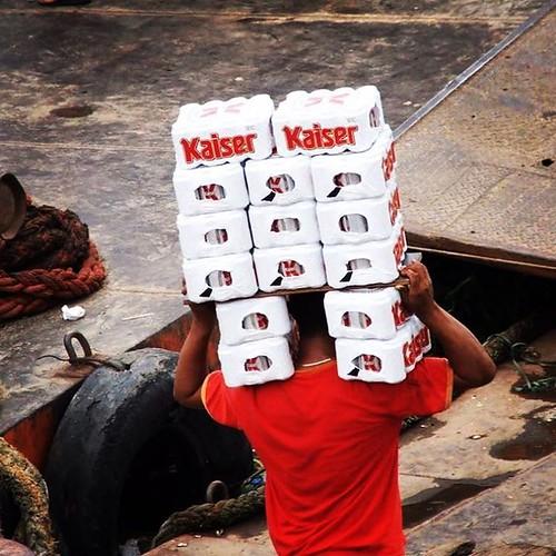 Cena inesquecível, clicada no Porto de Manaus, em 2018: quinze caixas de Kaiser (de Kaiser, senhoras e senhores!) no lombo.