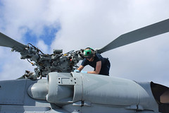 Aviation Electronics Technician 3rd Class Austin Luna conducts maintenance on an MH-60R helicopter aboard USS Kidd (DDG 100), March 16. (U.S. Navy)