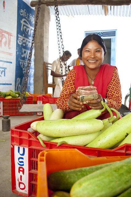 A woman smiles while holding money next to a crate full of vegetables.
