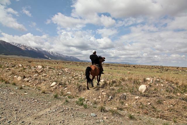 A man on horseback went into grassland, Barkol バルクル、草原に去っていく馬に乗った男性