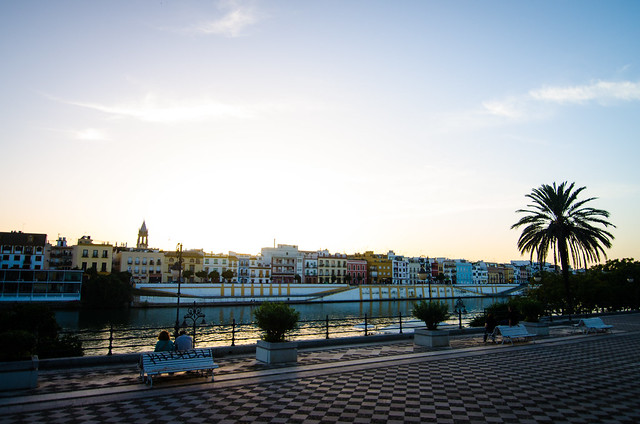 A lovely sunset view of colorful buildings and the Guadalquivir River in Sevilla.