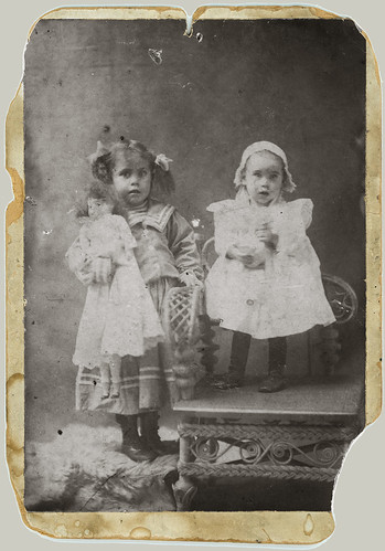 Two children and a rattan chair and a doll