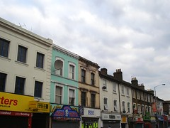 A view of the upper storeys of a terrace of shops, on a cloudy but bright day.