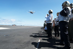 Japanese visitors aboard USS George Washington (CVN 73) observe an F/A-18E Super Hornet from the Eagles of Strike Fighter Squadron (VFA) 115 perform a low-altitude pass of the aircraft carrier in the Philippine Sea, Aug. 20. (U.S. Navy photo by Mass Communication Seaman Beverly Lesonik)