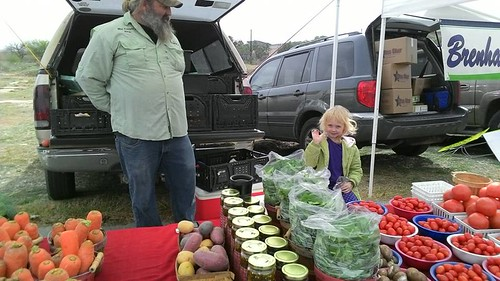 Anthony Micheli and daughter Scarlett stand ready to sell their vegetables at a Texas Farmers Market. The vegetables are grown on Micheli and his wife's (Brittany Davis) niche market operation financed by an FSA Microloan.