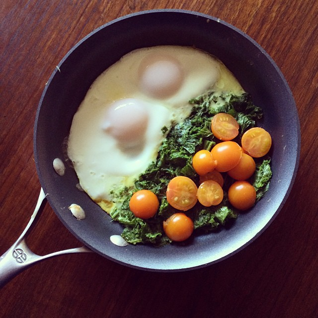Mustard greens, sungold tomatoes, and two sunny-side eggs.
