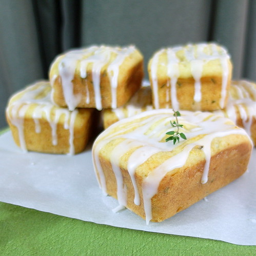 6 individual Lemon Thyme Tea Cakes staked two high on white paper. Glaze is dripping down to paper. A fresh thyme garnish is on top of front cake.