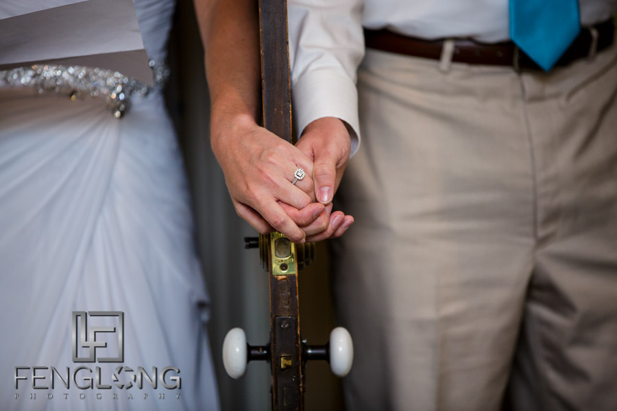 Bride and groom hold hands between a door for a first look