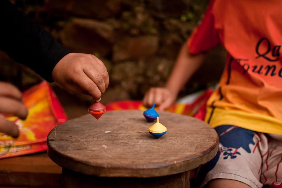 Niños se divierten con trompitos de juguete sobre una butaca mientras esperan la hora de comer en el pequeño pueblo de Itá Verá.  (Elton Núñez)