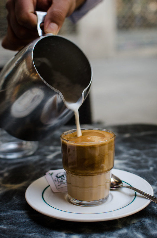 A waiter pours a perfect cafe con leche at Cafe Bib-Rambla.