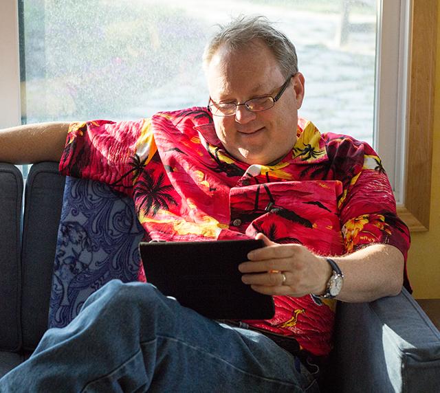 man reading on Amazon Fire tablet, wearing bright Hawaiian shirt