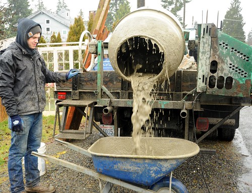 Brandon cleaning the concrete mixer using water and a wheelbarrow, specially set up portable mixer truck, for fence installation, raining, Seattle, Washington, USA