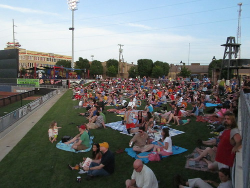 Fans sit in the right-field lawn at ONEOK stadium to watch the Tulsa Drillers
