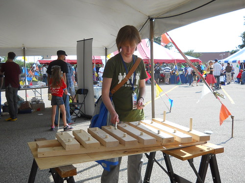 Emily makes music with a wooden xylophone from All Hands Active